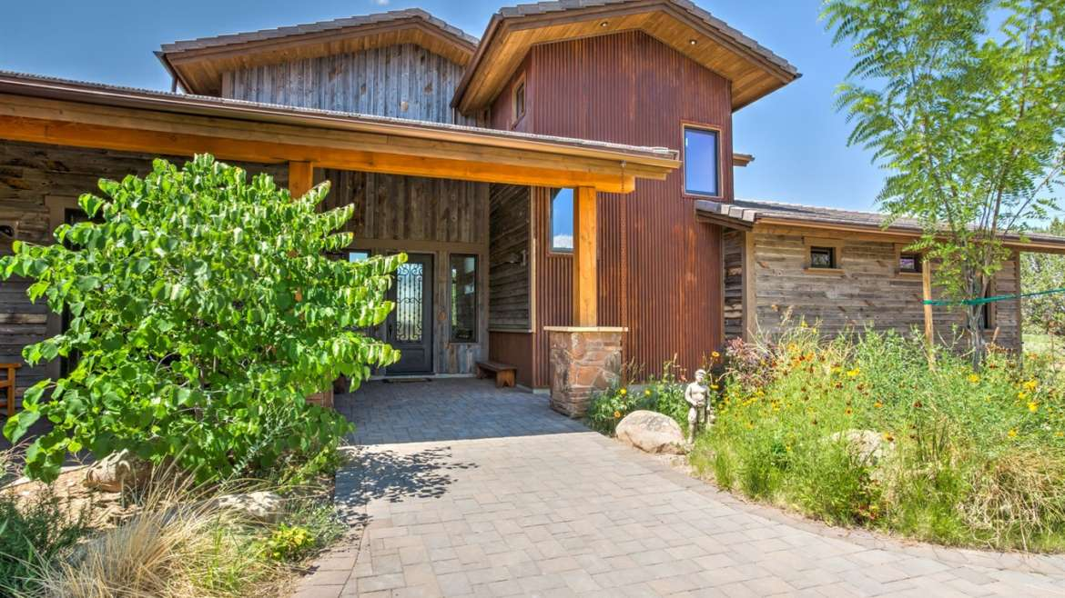 Combination of reclaimed wood siding, stone and metal used on this beautiful home